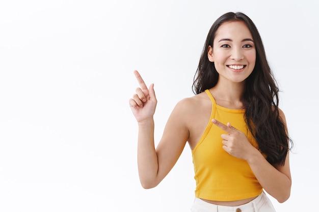 Taille-up aantrekkelijke jonge aziatische vrouwelijke student die naar het buitenland reist tijdens het onderwijsprogramma, de wereld ziet, er gefascineerd en gelukkig uitziet, naar de linkerbovenhoek wijst en zorgeloos naar de camera kijkt