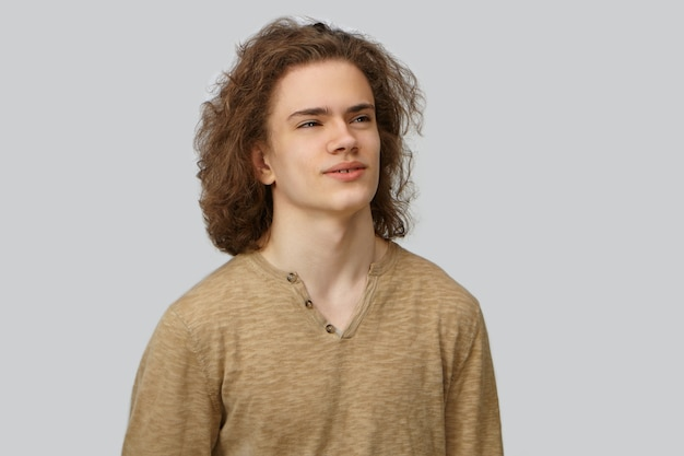 Taille-up geïsoleerde foto van knappe jonge man met losse krullende kapsel en glad schoon gezicht zijwaarts kijken met doordachte dromerige glimlach. menselijke gezichtsuitdrukkingen, emoties en gevoelens