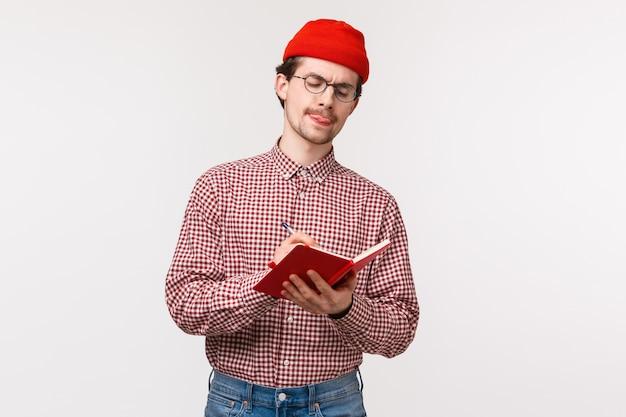 Taille-up portret creatieve hipster man in rode muts, bril, stick tong nadenkend tijdens het schrijven van notitie in notitieblok, lijst maken, helpen bij het oplossen van vergelijking voor jongere broer, staan
