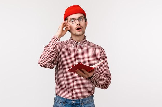 Taille-up portret geeky en creatieve man in rode muts, bril heeft een geweldig geweldig idee, raakt de tempel aan en ziet er geïnspireerd uit terwijl hij aantekeningen maakt in een notitieblok, een vergelijking maakt, op een witte muur staat