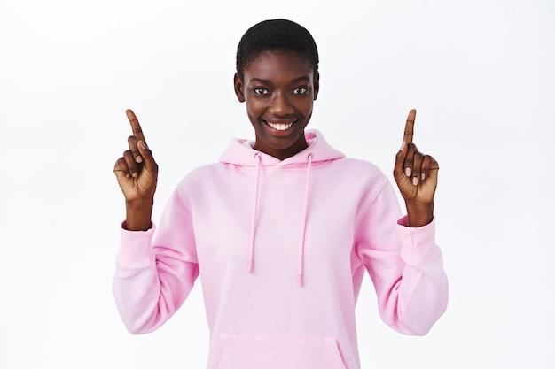 Taille-up portret glimlachend vriendelijk ogende aantrekkelijke afro-amerikaanse vrouw in roze hoodie