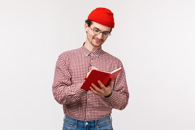 Taille-up portret grappige schattige bebaarde man rode muts, bril, notities opschrijven tijdens lezing, lijst van kruidenierswaren maken of dagboek hebben, lachend tevreden als bezig met project, witte muur