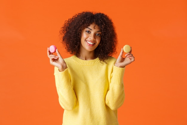Taille-up portret mooie jonge afro-amerikaanse vrouw met krullend afro kapsel, met twee macrons