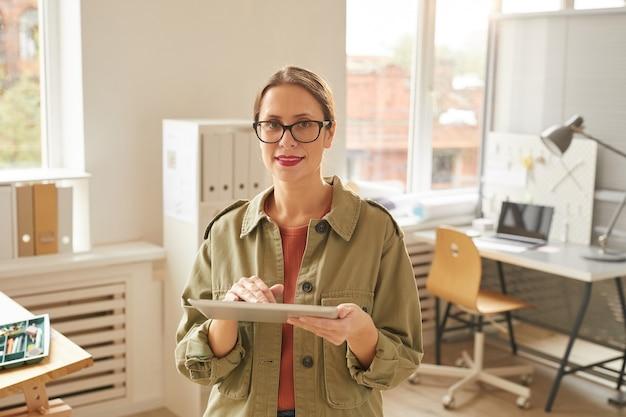 Taille-up portret om moderne jonge vrouw met behulp van digitale tablet en terwijl staande op kantoor verlicht door zonlicht,