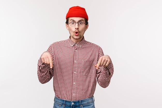 Taille-up portret opgewonden en verrast geamuseerde knappe kaukasische hipster in muts en bril die iemand vertelt wat hij in de online winkel heeft gevonden, wijzende vingers vertellen om snel een kijkje te nemen