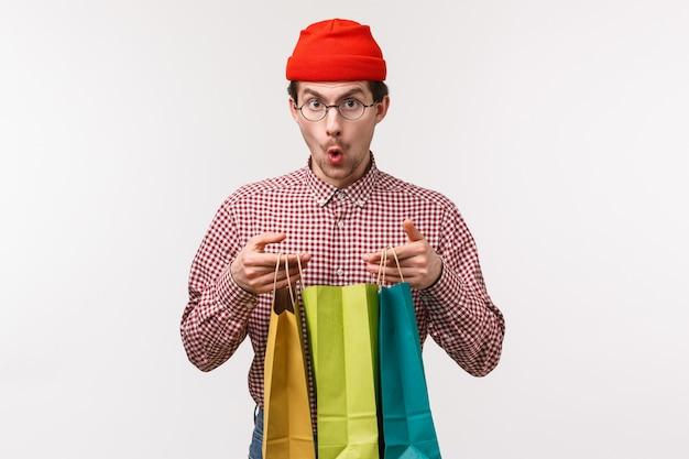 Taille-up portret opgewonden en verrast knappe jonge man met snor, draagt een bril en muts, kijkt verbaasd camera zeg wauw als open boodschappentassen met geschenken, staan