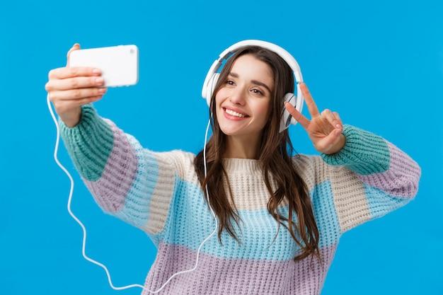 Taille-up portret schattige en tedere, mooie charismatische vrouw die selfie op smartphone neemt
