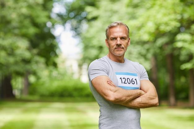 Taille-up portret shot van zelfverzekerde kaukasische senior sportman die deelneemt aan de zomermarathon staande in park met gekruiste armen, kopieer ruimte