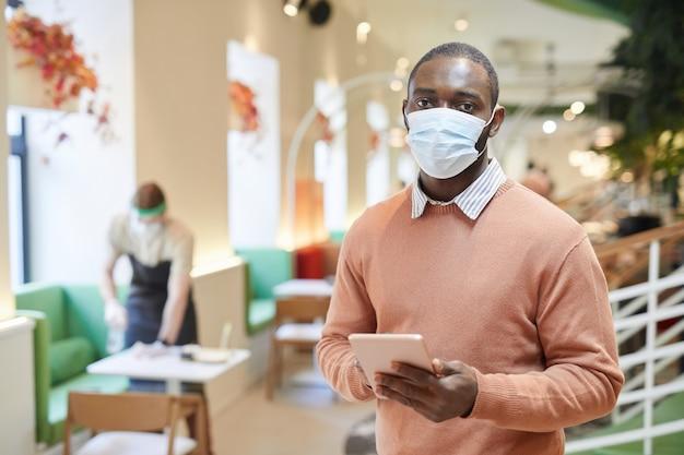 Taille-up portret van afro-amerikaanse man met masker en camera kijken tijdens het gebruik van tablet in café interieur, kopieer ruimte