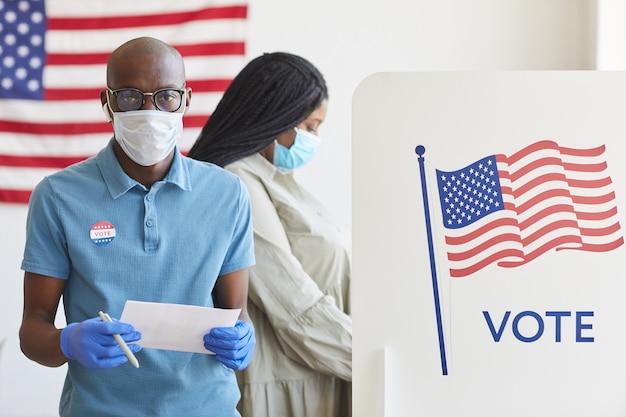 Taille-up portret van afro-amerikaanse man permanent door stemhokje versierd met vlag van de vs en op post-pandemische verkiezingsdag, kopie ruimte