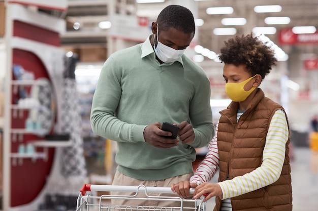 Taille-up portret van afro-amerikaanse vader en zoon die maskers dragen terwijl ze samen winkelen in de supermarkt en smartphone gebruiken om boodschappenlijst te controleren