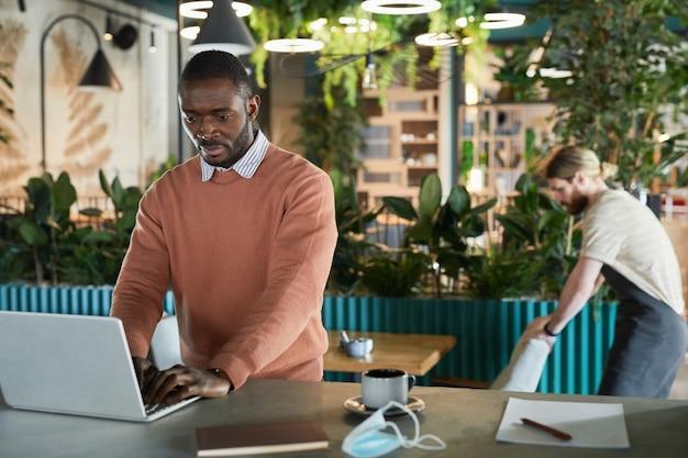 Taille-up portret van afro-amerikaanse zakenman die laptop gebruikt terwijl hij aan de bar werkt in een milieuvriendelijk café-interieur versierd met verse groene planten, kopieer ruimte