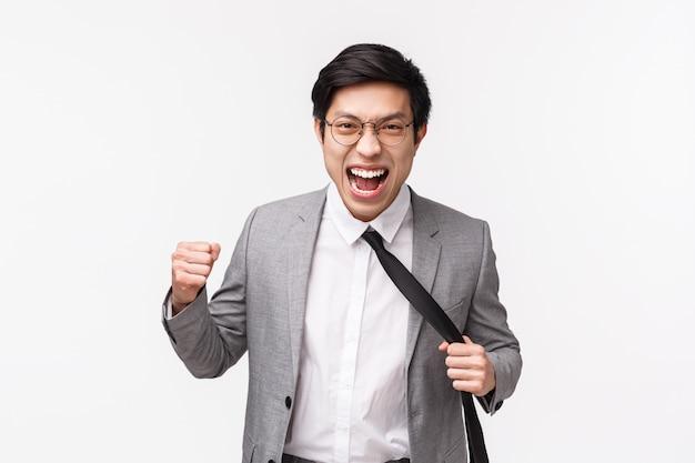 Taille-up portret van agressieve, boze en pissige jonge aziatische officemanager die geduld verliest, gebalde vuist wil iemand in het gezicht slaan, grimassen overschat, stropdas aanspannen, op een witte muur