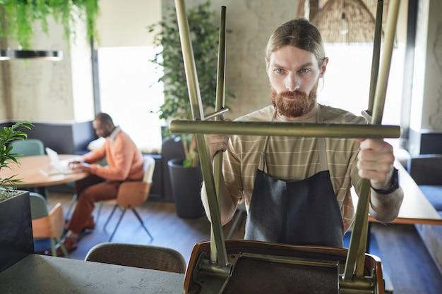 Taille-up portret van bebaarde cafémedewerker die meubels schikt terwijl hij zich voorbereidt op opening in de ochtend, kopieer ruimte