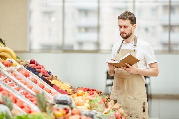 Taille-up portret van bebaarde man met schort staande door groenten en fruit staan op boerenmarkt tijdens de verkoop van verse producten