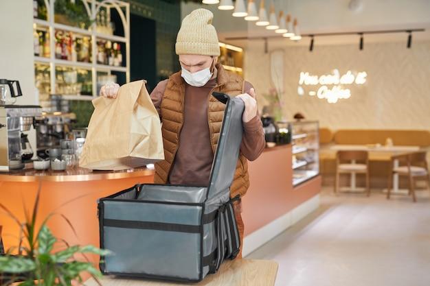 Taille-up portret van bezorger met masker terwijl hij bestellingen inpakt om in café-interieur te verpakken, kopieer ruimte