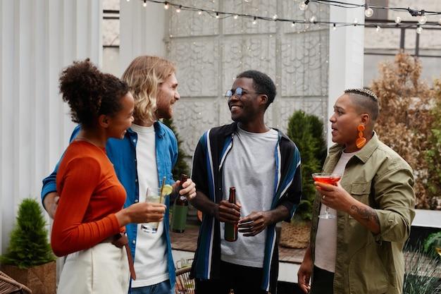 Taille-up portret van diverse groep jonge mensen die plezier hebben op een buitenfeest op het dak en chatten