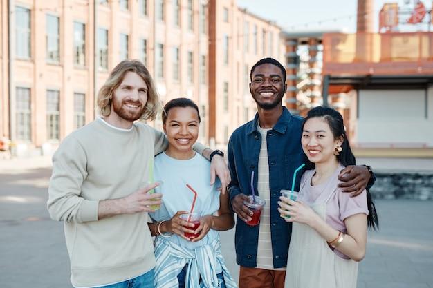 Taille-up portret van diverse groep mensen die naar de camera glimlachen terwijl ze genieten van de zomer in de stad