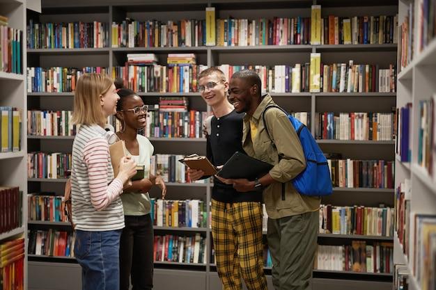 Taille-up portret van diverse groep studenten die aan het chatten zijn terwijl ze in de kopieerruimte van de schoolbibliotheek staan