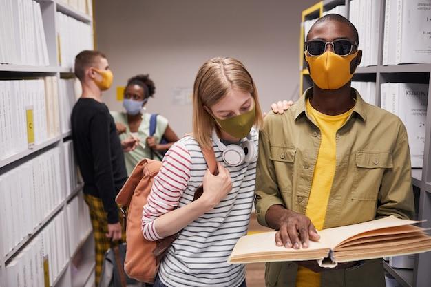 Taille-up portret van diverse groep studenten in bibliotheek met blinde man op de voorgrond