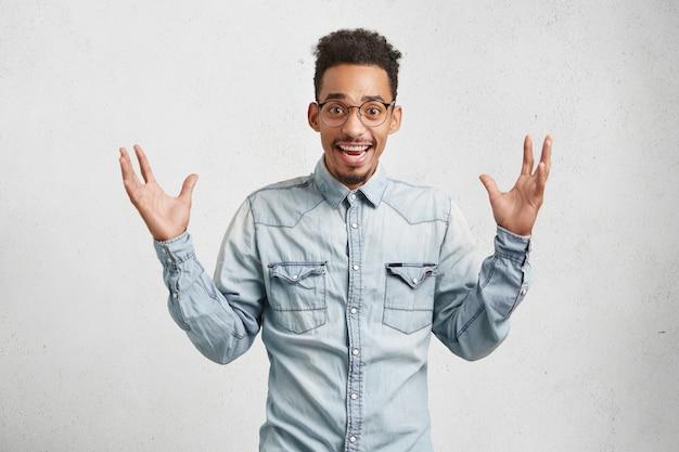 Taille-up portret van dolgelukkig modieuze man met trendy kapsel, draagt denim overhemd, steekt handen op