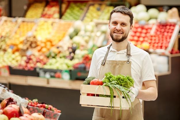 Taille-up portret van een bebaarde man met een doos met groenten en lachend tijdens de verkoop van verse producten op de boerenmarkt