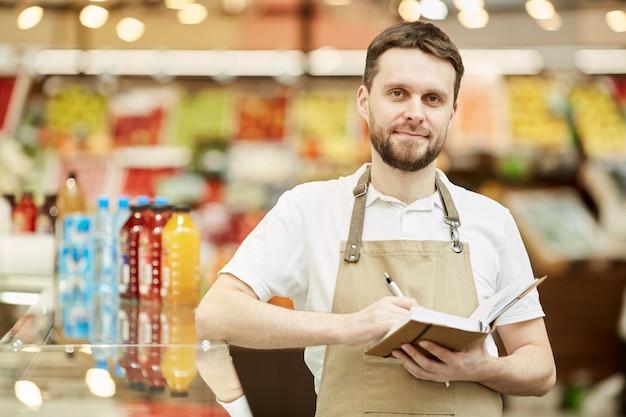 Taille-up portret van een bebaarde man met schort en notitieboekje vast te houden terwijl hij in de supermarkt staat
