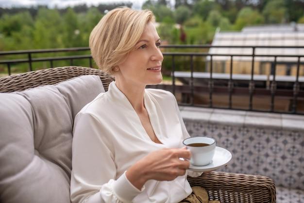 Taille-up portret van een dromerige stijlvolle dame met een schotel en een kopje in haar handen zittend in de leunstoel