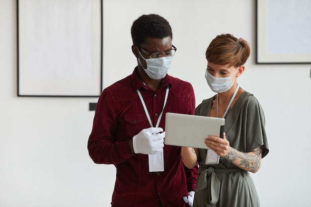 Taille-up portret van een getatoeëerde jonge vrouw en een afro-amerikaanse man die beide maskers dragen tijdens het gebruik van een digitale tablet en een kunstgalerie-tentoonstelling plannen,