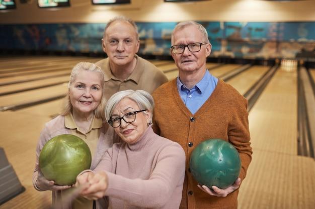 Taille-up portret van een groep senioren die selfie-foto's maken tijdens het bowlen en genieten van actief entertainment op de bowlingbaan