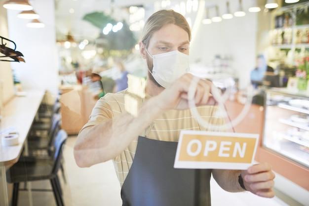 Taille-up portret van een jonge man met een masker terwijl hij 's ochtends een open bord op de glazen deur van het café hangt, kopieer ruimte