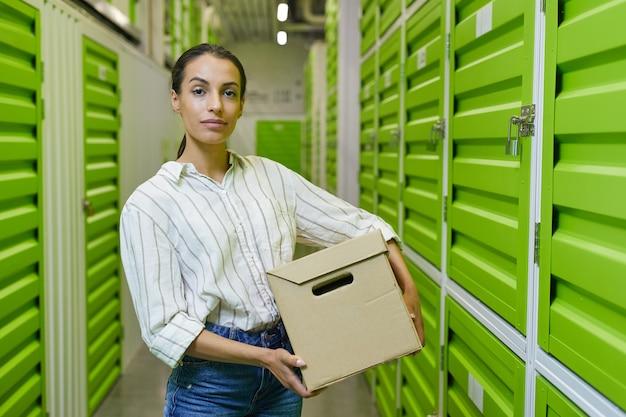 Taille-up portret van een jonge vrouw met kartonnen doos staan in zelfopslagfaciliteit en kopieer ruimte