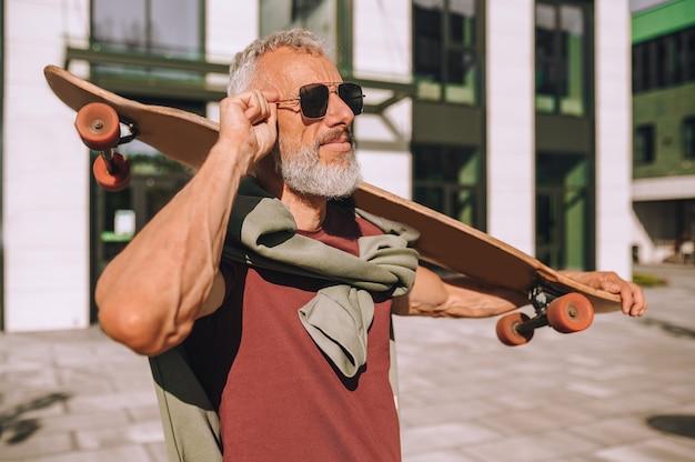 Taille-up portret van een rustige volwassen fit mannelijke skateboarder die het bord over de schouder houdt
