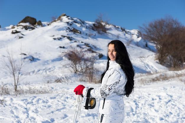 Taille-up portret van een vrouw met lang donker haar, gekleed in een wit skipak en glimlachend terug over de schouder naar de camera, een pauze nemen van het skiën op de met sneeuw bedekte berg op een heldere dag met zonneschijn