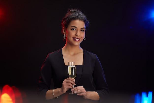 Taille-up portret van elegante midden-oosterse vrouw met champagne glas en lachend naar de camera terwijl staande tegen een zwarte achtergrond op feestje, kopieer ruimte