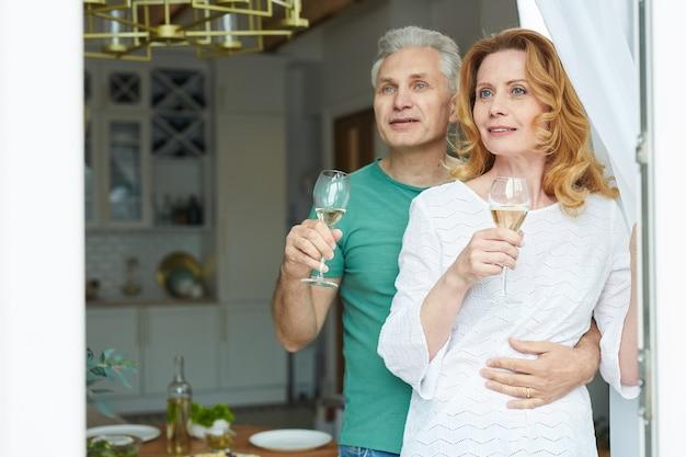 Taille-up portret van elegante volwassen paar genieten van champagne terwijl ze uit raam naar terras kijken, kopieer ruimte