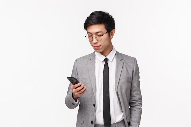 Taille-up portret van ernstig ogende knappe stijlvolle zakenman in grijs pak, hand in zak houden, terloops met behulp van mobiele telefoon, sms'en zakenpartner, met behulp van smartphone, op een witte muur
