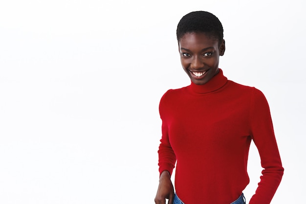 Taille-up portret van flirterig, knap afrikaans-amerikaans vrouwelijk model in rode coltrui met schattige stralende glimlach