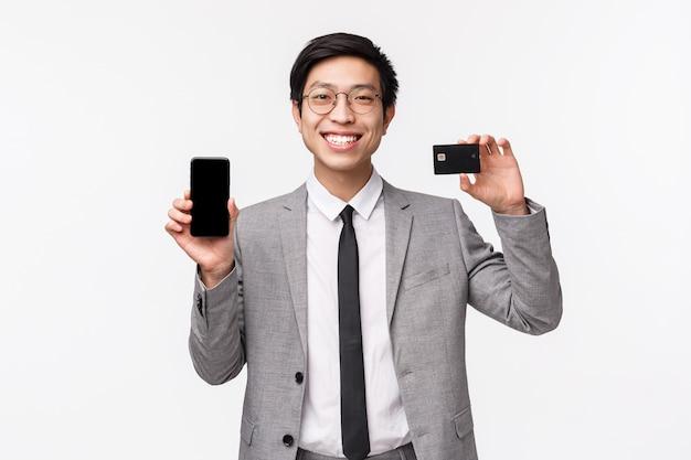 Taille-up portret van gelukkige, goed uitziende aziatische zakenman in grijs pak, bril met weergave van mobiele telefoon en creditcard, tevreden glimlachend, advies download bank-app, gebruik niet-contante betaling