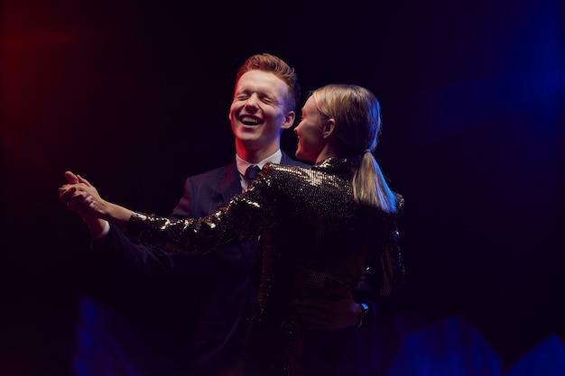Taille-up portret van gelukkige jonge paar samen dansen terwijl u geniet van feest op prom night tegen donkere achtergrond, kopieer ruimte