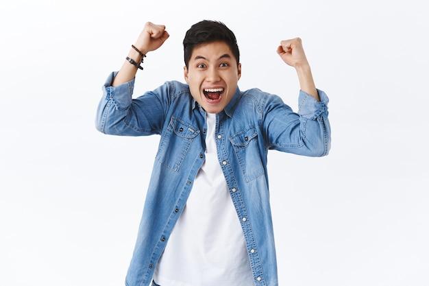 Taille-up portret van gelukkige, opgewonden jonge lachende man schreeuwen hoera of ja, handen opsteken, vuist pomp in vreugde, vreugde over overwinning, doel bereiken, overwinning of succes vieren, witte muur