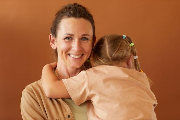 Taille-up portret van gelukkige rijpe moeder die dochter terwijl staande tegen een effen bruin oppervlak in de studio en lachend naar de camera