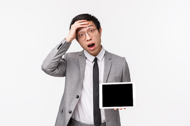 Taille-up portret van geschokte en verbaasde jonge aziatische man in pak realiseerde iets belangrijks, onthoud, raak ontzag voorhoofd aan, met digitale tablet-display, op een witte muur