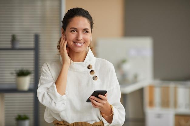 Taille-up portret van glimlachende elegante zakenvrouw met behulp van draadloze oortelefoons tijdens het spreken via de telefoon thuis of op kantoor, kopieer ruimte