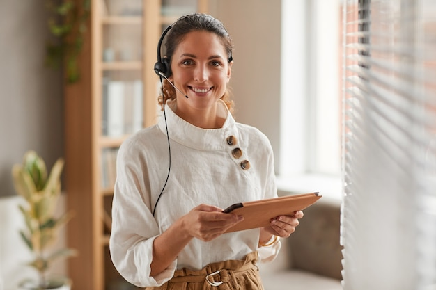 Taille-up portret van glimlachende zakenvrouw hoofdtelefoon dragen en camera kijken tijdens de onlinevergadering in kantoor, kopieer ruimte