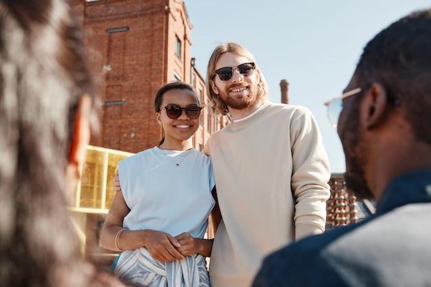 Taille-up portret van hedendaags jong stel dat vrienden buiten in de stad ontmoet, beiden met een zonnebril