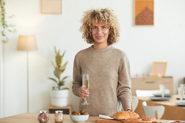 Taille-up portret van hedendaagse gemengd ras vrouw met champagne glas en tijdens het koken voor etentje binnenshuis,