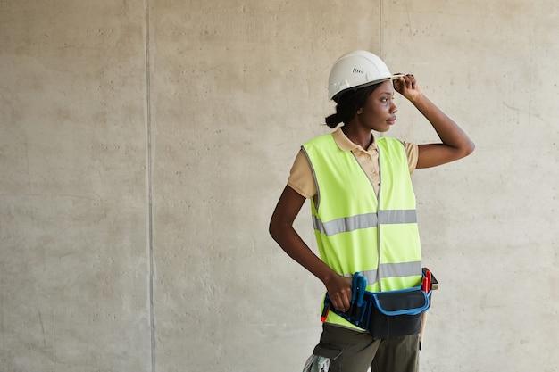 Taille-up portret van jonge afro-amerikaanse vrouw die op de bouwplaats werkt en wegkijkt kopie ...