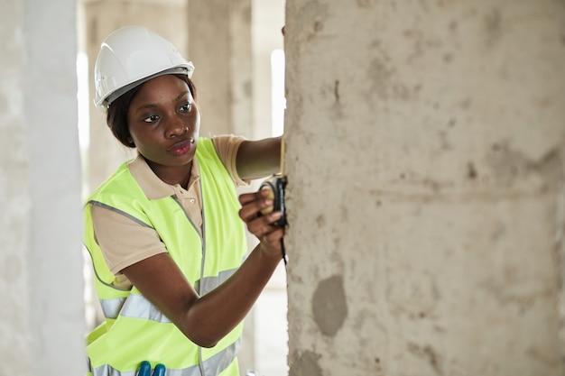 Taille-up portret van jonge afro-amerikaanse vrouw die werkt op de bouwplaats in technische kopieerruimte