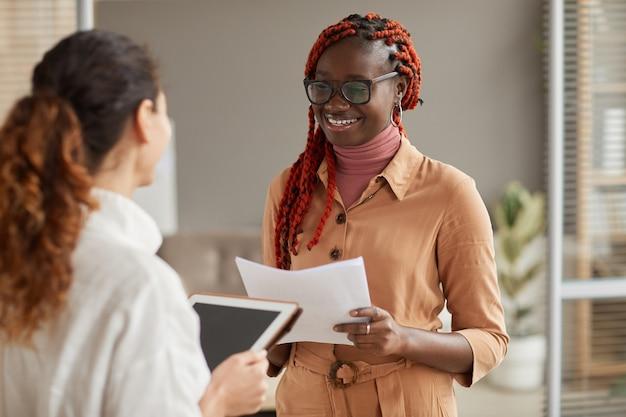 Taille-up portret van jonge afro-amerikaanse zakenvrouw praten met vrouwelijke manager en vrolijk glimlachen terwijl staande in moderne kantoor interieur